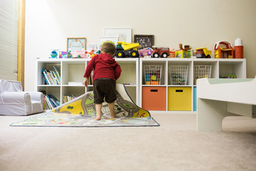 Toddler cleaning up playroom