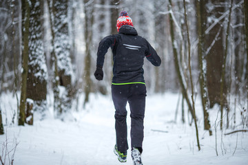 Photo from back of running athlete among trees in winter forest