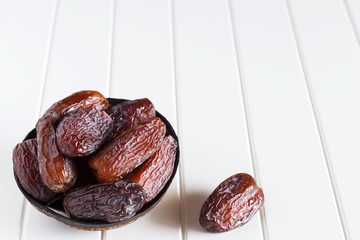 Fresh dates Medjool in wooden coconut bowl. White background.