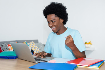 Jubelnder afrikanischer Student am Computer