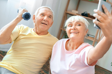 Senior couple exercise together at home health care selfie photos with dumbbell