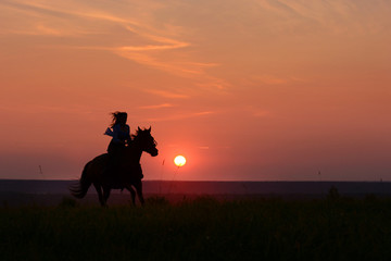 Galloping horse on sunset. Horseback woman riding gallop with red rising sun on horizon. Horse hiking on beautiful colorful background with equine and girls silhouette.