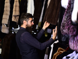 Man with beard and mustache looking for fur coat.