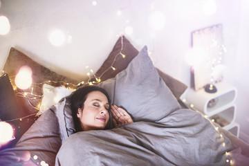 junge Frau beim Schlafen im Bett Ambiente Lichterkette