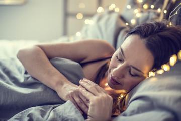 Junge Frau beim Schlafen Ambiente Bett Schlafzimmer