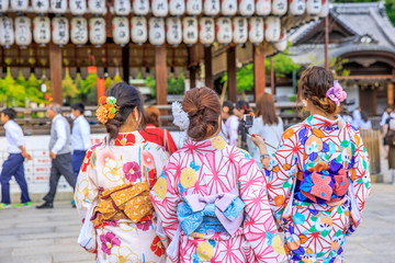 Three Japanese women in kimono take picture of paper lanterns of Yasaka Shrine in Kyoto, Japan. Gion Shrine is one of the most famous shrines in Kyoto between Gion District and Higashiyama District.