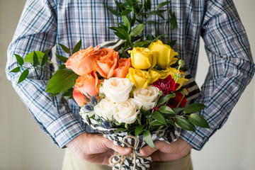 Man giving away bouquet of spring roses