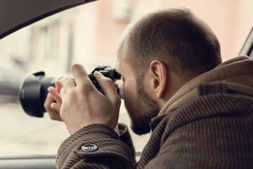 Investigator or private detective or reporter or paparazzi sitting in car and taking photo with professional camera