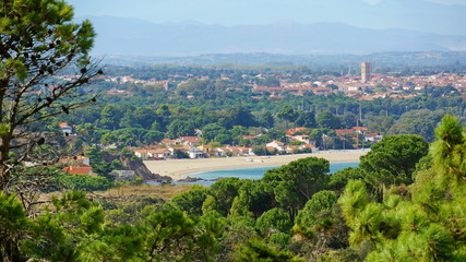 Mediterranean beach of the Racou in Argeles-sur-Mer with the village in background, Roussillon, Pyrenees Orientales, France
