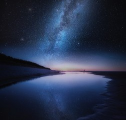 Sea shore in night with stars reflected in water