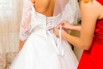 Helping the bride dress in wedding dress.