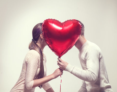 Valentine's day. Happy joyful couple holding heart shaped air balloon and kissing. Love