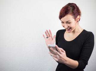 Young girl holding mobile phone in hand, expression of face positively surprised with gentle smile, white background