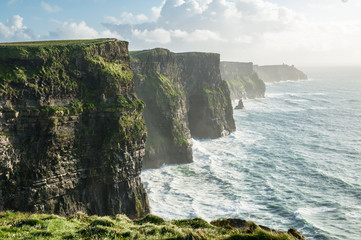 The Cliffs of Moher, Irelands Most Visited Natural Tourist Attraction, are sea cliffs located at the southwestern edge of the Burren region in County Clare, Ireland. Wall mural