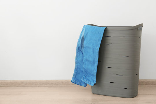 Bin with dirty clothes prepared for laundry indoors