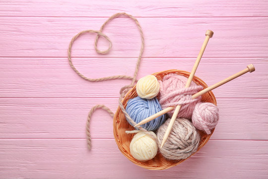Balls of knitting yarn in basket and heart made of thread on wooden background