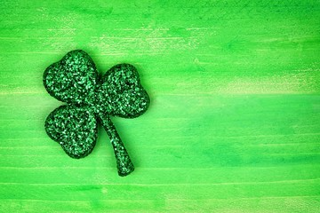 Single St Patricks Day glittery shamrock over a green wood background