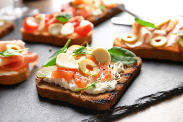 Tasty bruschetta with olives and salmon on slate plate