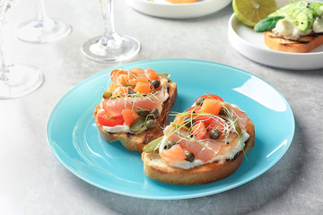 Tasty bruschettas with prosciutto on plate