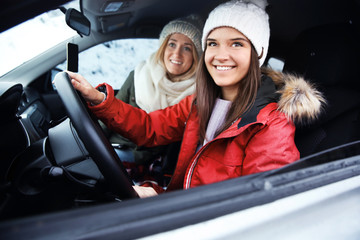 Happy female tourists travelling by car