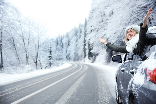Happy tourist enjoying the beauty of snowy landscape while travelling by car