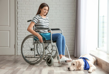 Young woman in wheelchair with dog indoors