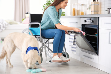 Woman in wheelchair cooking with service dog by her side indoors