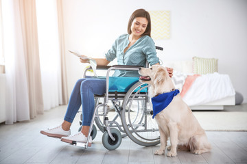 Woman in wheelchair reading newspaper with service dog by her side indoors