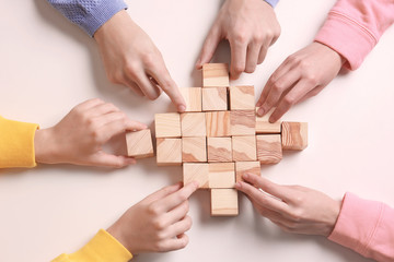 Group of people with wooden cubes on white background. Unity concept