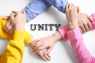 People holding hands together around word UNITY on white background