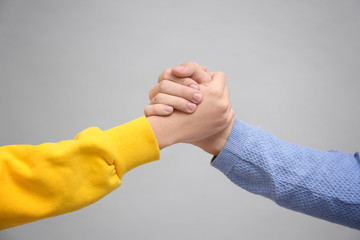 Man and woman holding hands together on light background. Unity concept