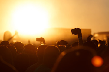 Silhouette of smartphone in a hand over crowd.