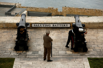 Re-enactors of the Malta Heritage Trust prepare a cannon to fire the noon-day gun, a naval tradition dating back to the 19th century when ship-masters on board vessels needed something to calibrate their ship clocks by, at the Saluting Battery overlooking