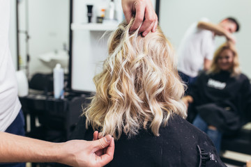 Foto op Aluminium Kapsalon Beautiful hairstyle of young woman after dying hair and making highlights in hair salon.