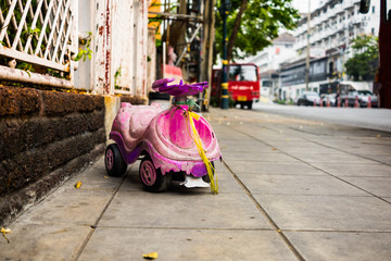 Old toy car for kid on the sidewalk.