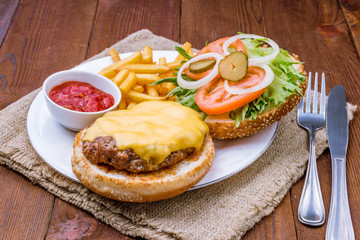 open cheeseburger on wooden background