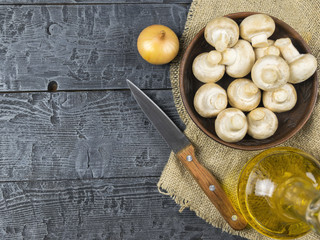 Fresh mushrooms in a clay bowl with a knife on a piece of burlap on a wooden table. The view from the top.