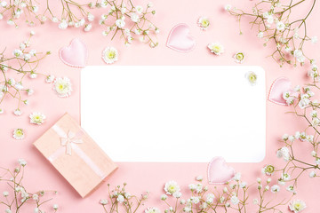 Blank paper card with gypsophila flowers and gift box on pink background. Space for text. Flat lay style.