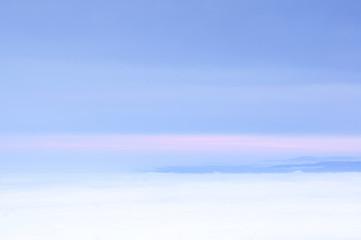 Pastell Himmel in den Farben blau, weiß und zart rosa mit Berglandschaft am Horizont als Silhouette.