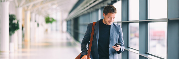 Man holding phone - young businessman using smartphone in airport. Casual urban professional business man texting cellphone happy inside office banner panorama with copy space on background. Wall mural