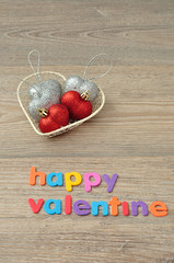 A wire basket filled with silver and red heart shape baubles and the words happy valentine