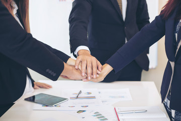 close up hand of business partnership people stacking hands finishing up meeting showing unity over office desk  , business teamwork concept'