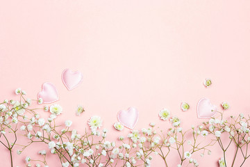Pink background with gypsophila flowers and hearts. Space for text.