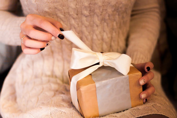 Woman open her present and pull decorative ribbon. Closeup view of gift