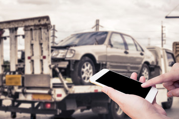 Hand using mobile smartphone for emergency roadside service with Broken car on tow truck after traffic accident background