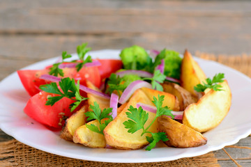 Fried potatoes with vegetables. Fried potato wedges, cooked broccoli, fresh tomato slices, red onion, green parsley on a serving plate and on a wood background. Vegetarian main course recipe. Closeup