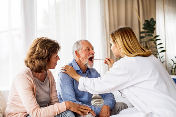 Female doctor examining a senior man.