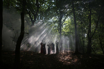 silhouette of a group of women in a dark forest with smoke