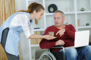 carer serving a cup of tea to patient