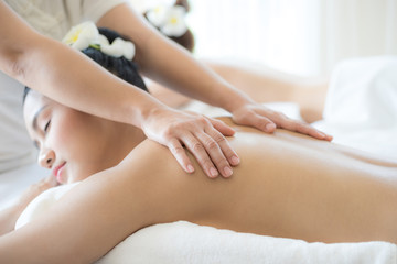beautiful and healthy young woman relaxing with back massage in spa salon